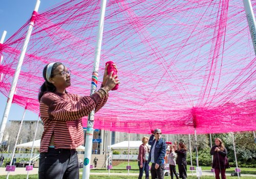 Student creating an art installation with pink yarn on UNC Asheville's Quad